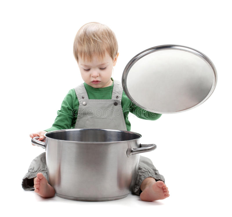 Baby looking inside saucepan. Isolated on white background royalty free stock photography