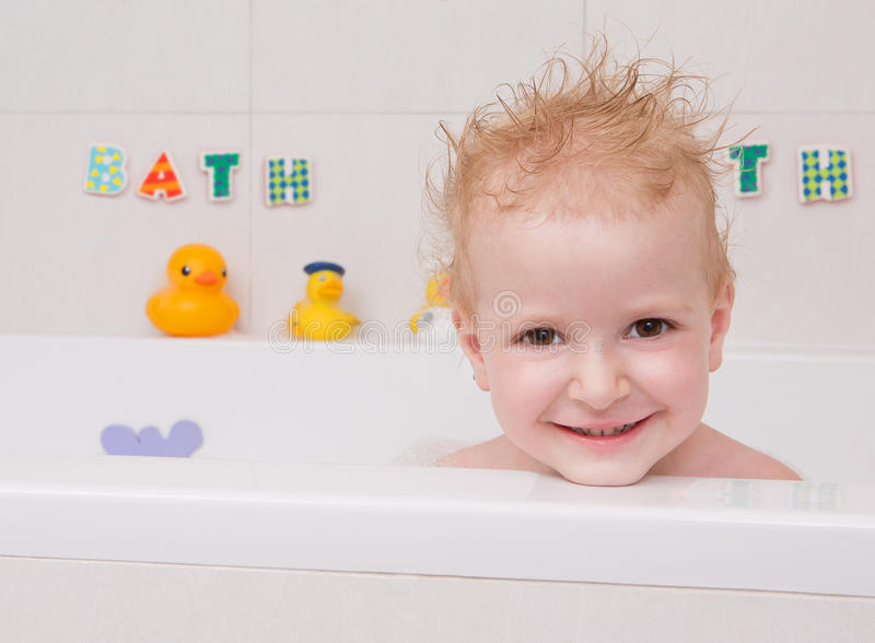 Baby looking out of the bath. Little girl in bath with rubber ducks royalty free stock images