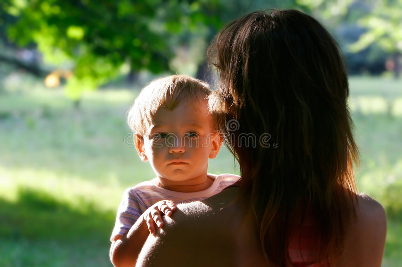 Baby looking over mother's shoulder royalty free stock photo