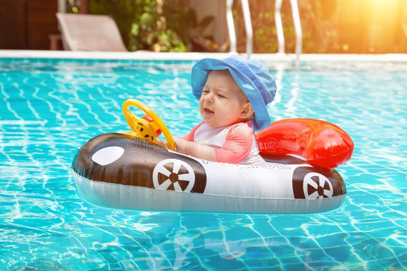 Baby love to swim. Summer vacation at sea. A little girl less than one year old is driving an inflatable boat in the shape of a stock image