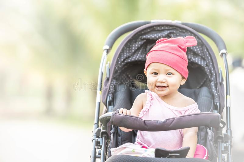 Baby lovely girl smiling and looking up to camera outdoors. Beautiful asian 6 months infant having happy time in the park royalty free stock images
