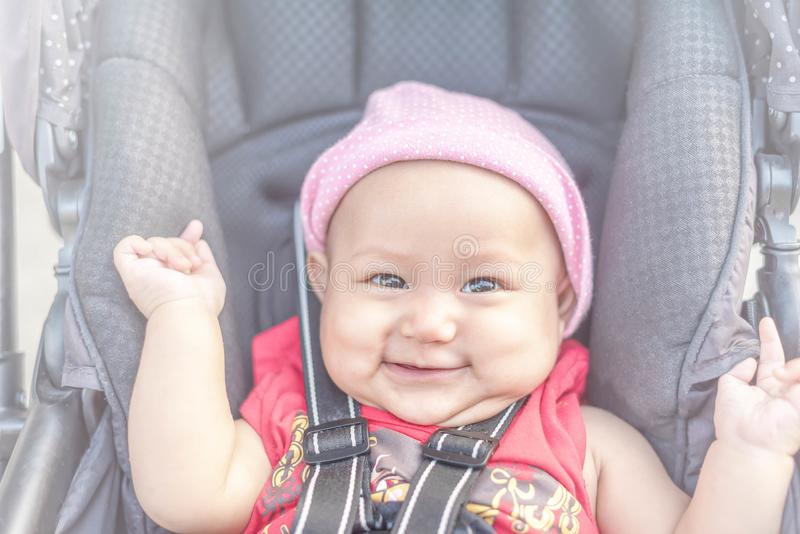 Baby lovely girl smiling and looking up to camera outdoors. Beautiful asian 6 months infant having happy time in th park stock photography