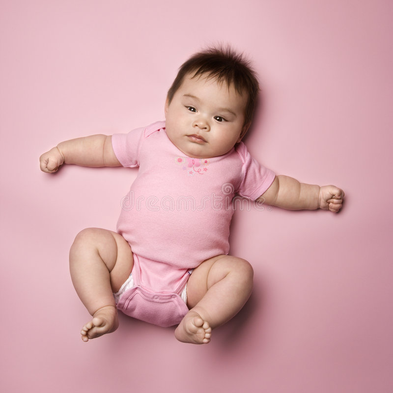 Baby lying on back. Asian baby lying on back lookin up at viewer with arms out to side