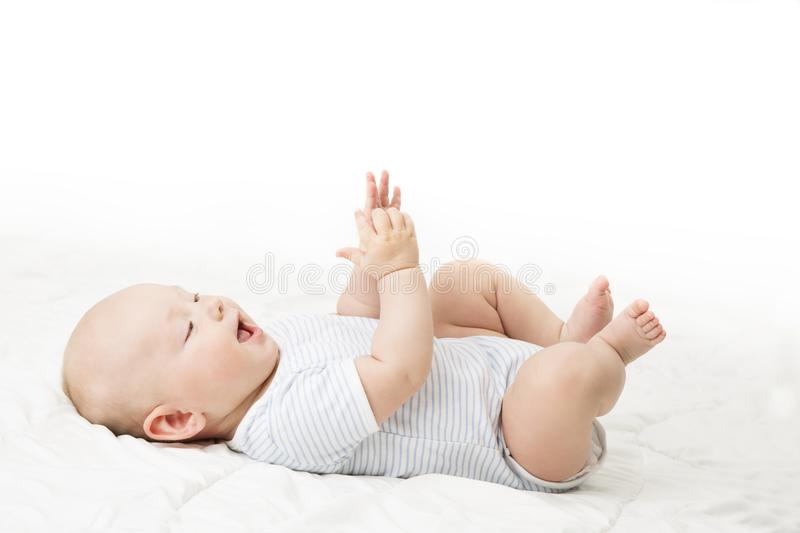 Baby Lying on Back, Happy Infant Kid in Blue Bodysuit, Beautiful royalty free stock image