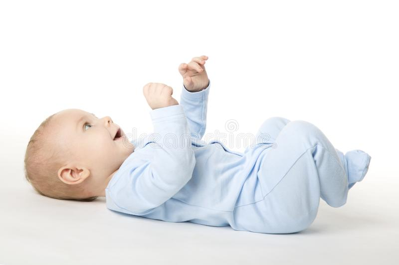 Baby Lying on Back, Happy Infant Kid Dressed in Blue Bodysuit. Beautiful Child Lie on White background looking up royalty free stock photo