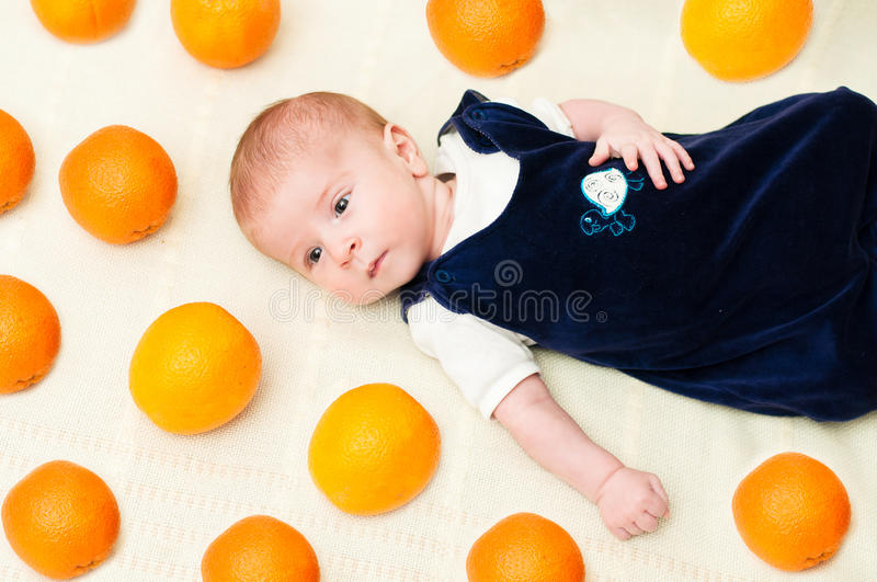 Baby lying on the bed with oranges stock photos