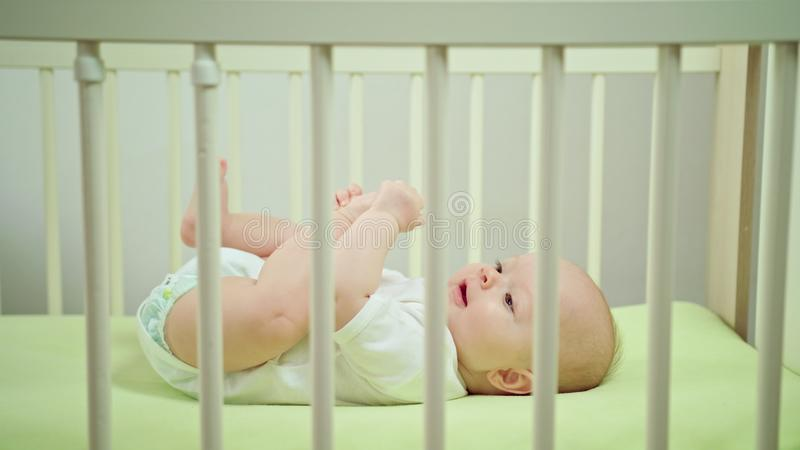 Baby Lying in a Crib at Home Eating its Toes. Baby`s lying on a green linen in a crib at home, eating its toes. Long shot stock photography
