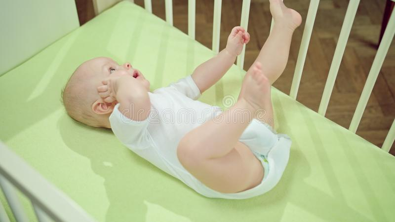 Baby Lying in a Crib at Home and Playing. Baby`s lying on a green linen in a crib at home, eating its finger and playing with its feet. Long shot from above stock photo