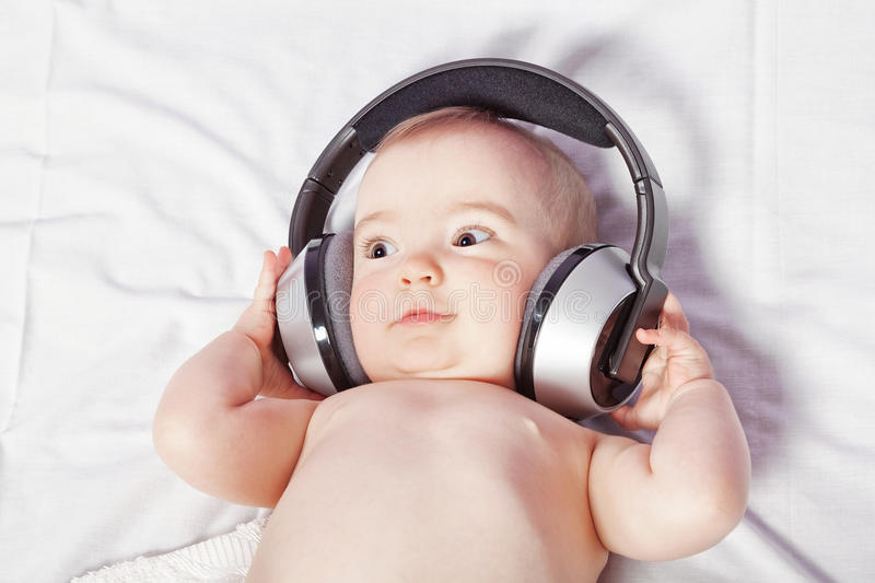 Baby lying down listening to music with wireless headphones. stock image
