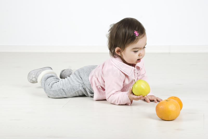 Baby Lying On Floor With Fruits Stock Images