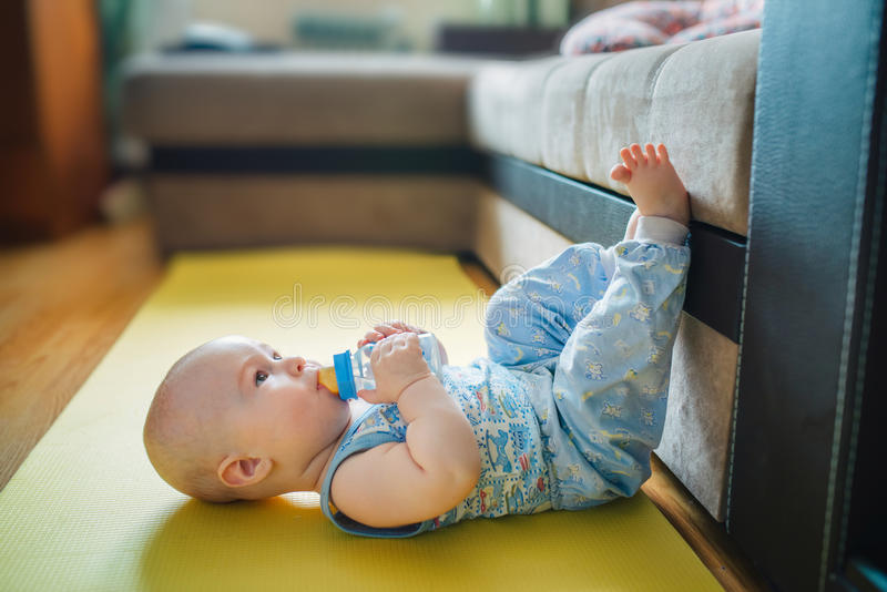 Baby lying on the floor with his feet up and drinking watter fro royalty free stock image