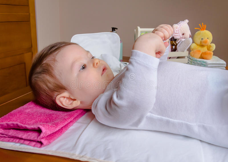 Baby lying playing with a children comb. Adorable baby lying playing with a children comb after the change of diaper stock photography