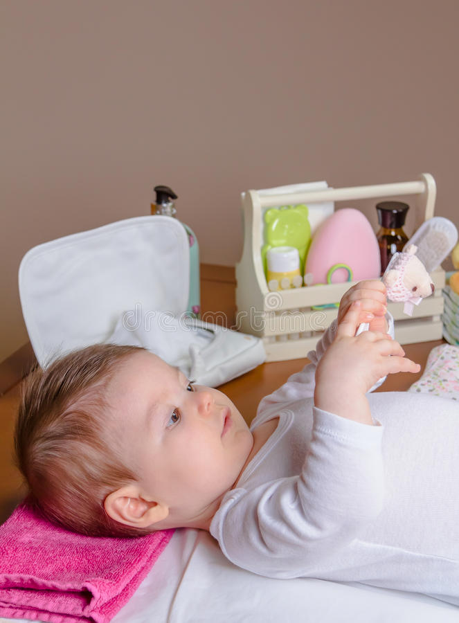 Baby lying playing with a children comb stock image
