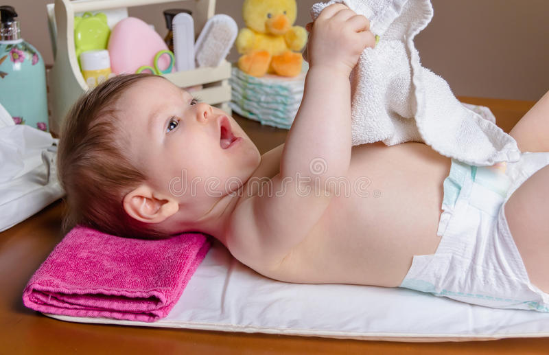 Baby lying playing with a small towel stock image