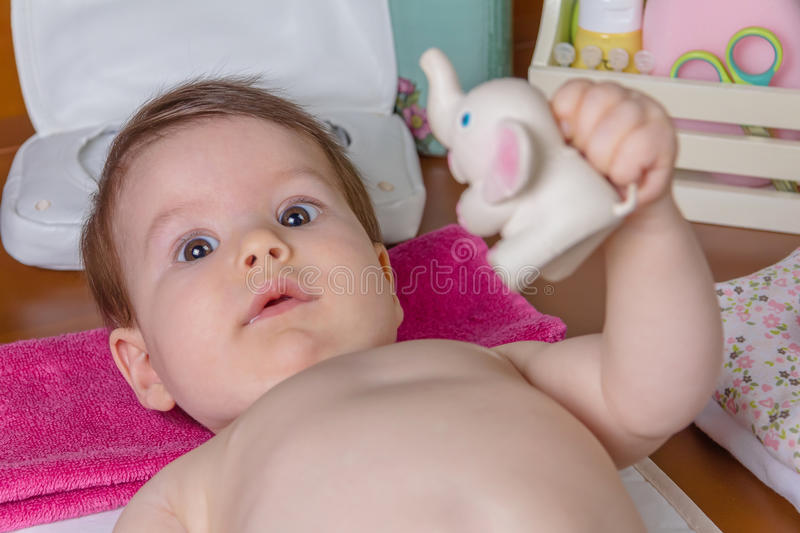 Baby lying playing with a toy rubber royalty free stock images