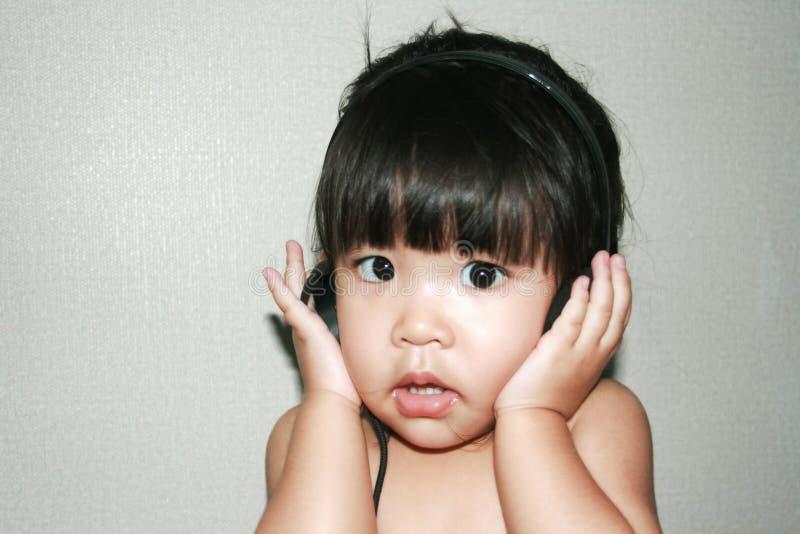 Baby lyssnar musik från headphonen arkivfoto