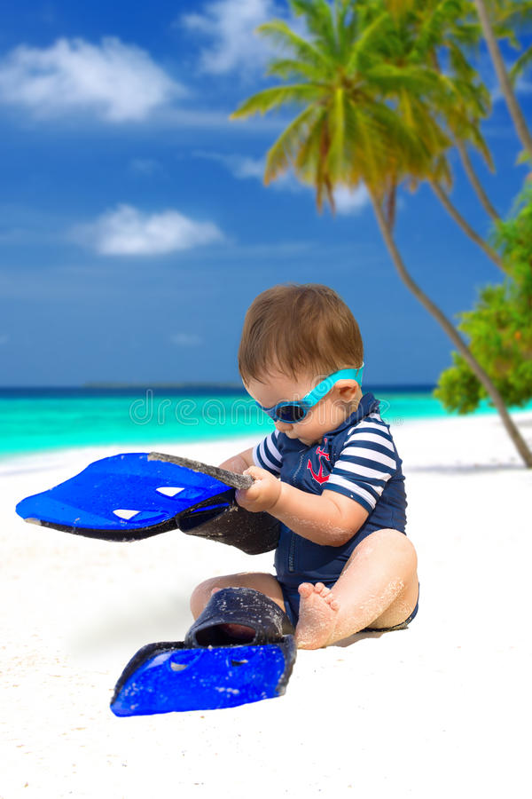 Baby on Maldives. Cute baby with diving costume or swimwear, sunglasses and flippers sitting on the tropical beach on Maldives stock photography