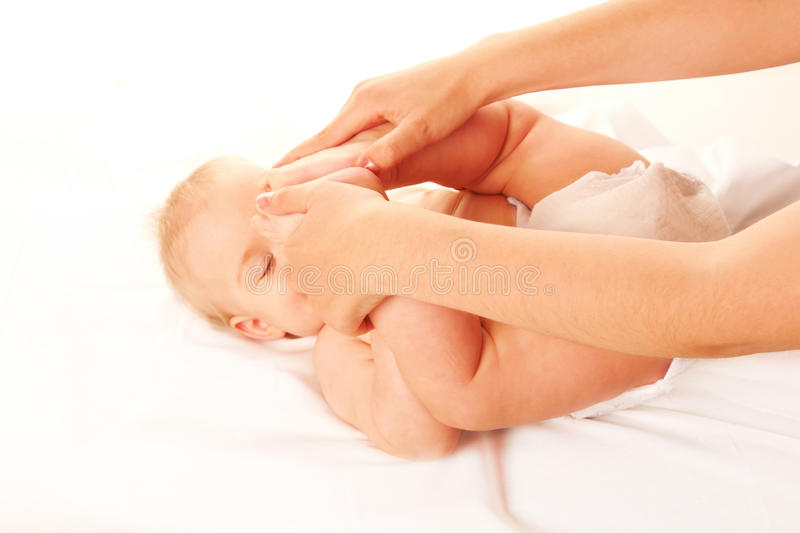 Baby massage. Baby feet touching his forehead. stock photos
