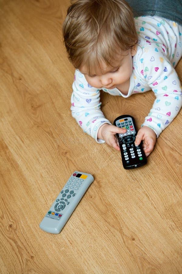 Baby met afstandsbedieningen stock foto's