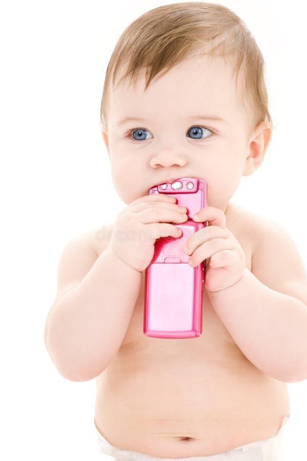 Baby met celtelefoon stock foto's