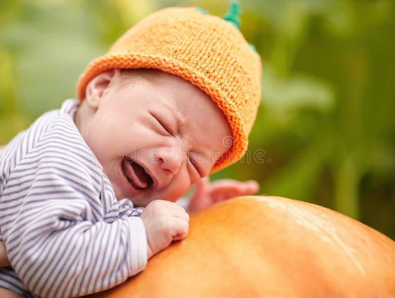 Baby met de slaap van de pompoenhoed op grote oranje pompoen royalty-vrije stock foto's
