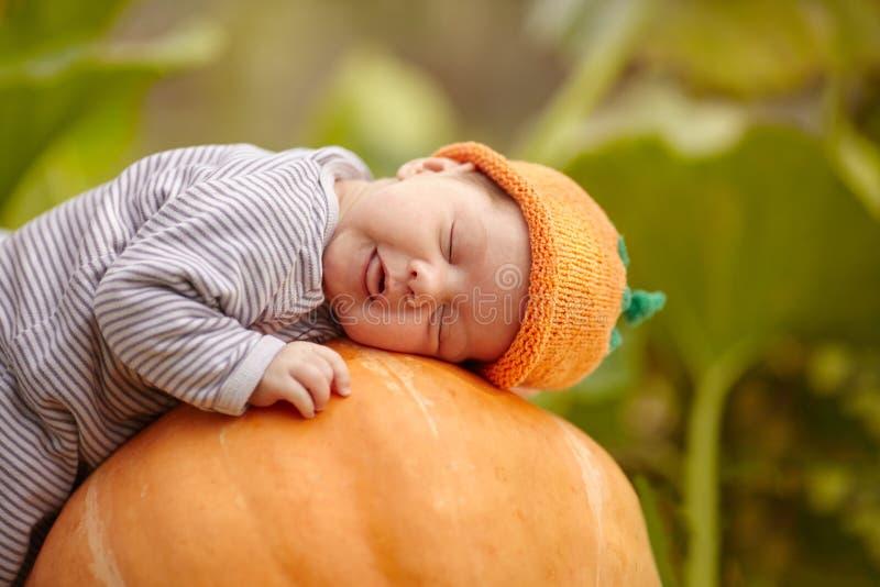 Baby met de slaap van de pompoenhoed op grote oranje pompoen royalty-vrije stock foto