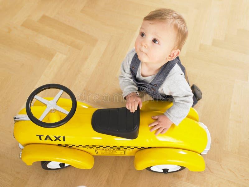 Baby met de Taxi van het Stuk speelgoed stock afbeelding