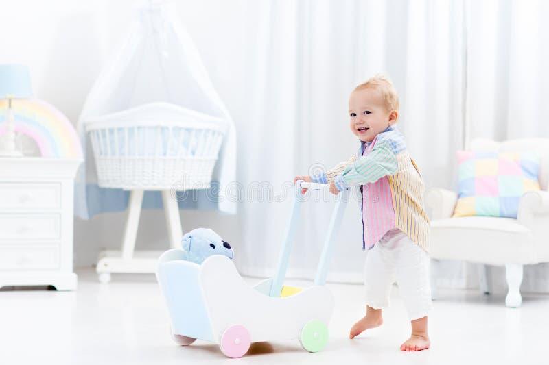 Baby met duwleurder in witte slaapkamer stock foto's