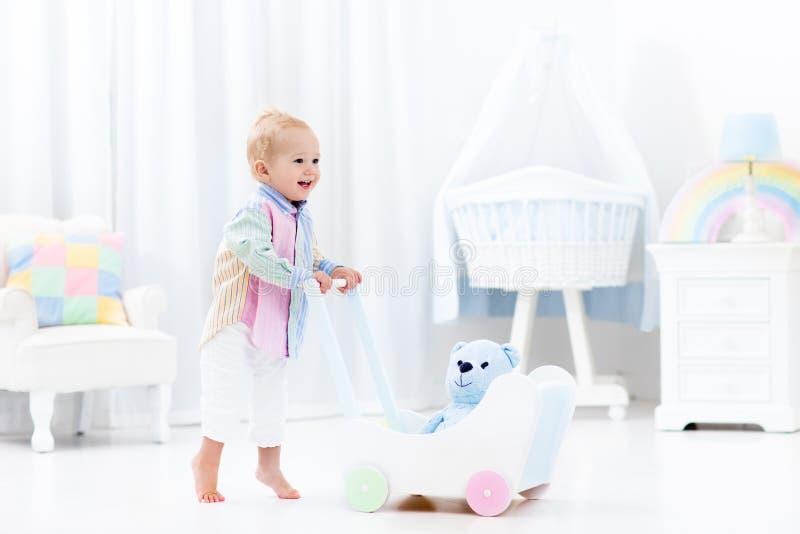 Baby met duwleurder in witte slaapkamer royalty-vrije stock fotografie