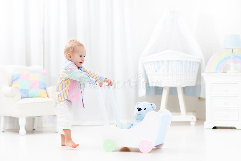 Baby met duwleurder in witte slaapkamer royalty-vrije stock afbeelding