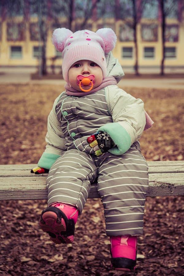 Baby met een fopspeenzitting op een bank stock fotografie