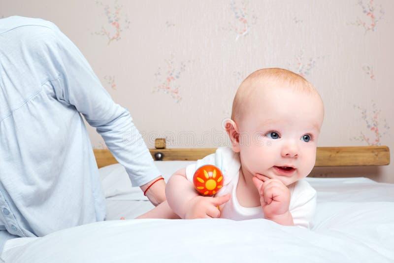 Baby met een stuk speelgoed in ruke Mamma volgende koesterende baby gelukkige familie, ca stock afbeeldingen