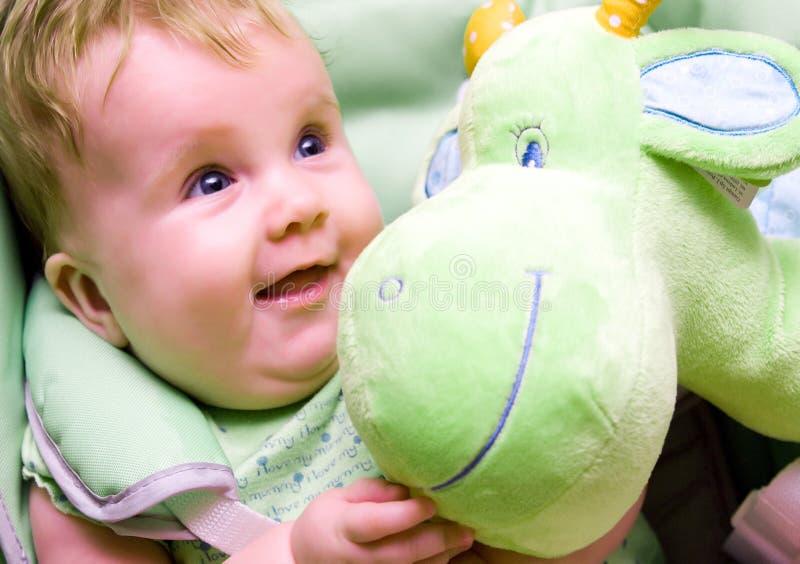Baby met groen zacht stuk speelgoed royalty-vrije stock foto