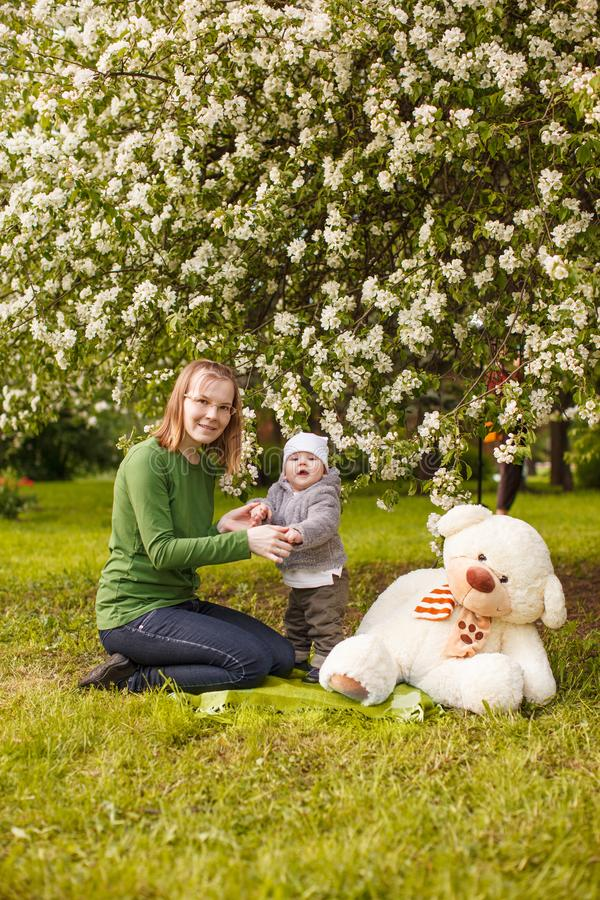 Baby met moeder in het park in de stralen van zonsondergang Peuter met mamma op de aard in openlucht Backlight De scène van de zo royalty-vrije stock foto's
