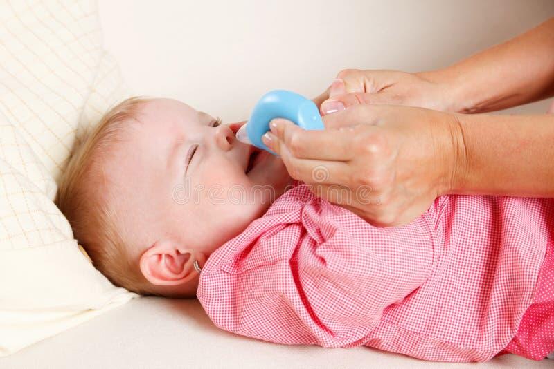 Baby met neusvacuüm stock foto's