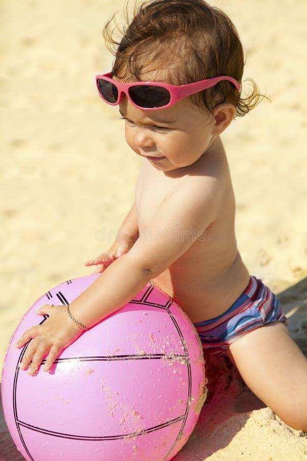 Baby met op het strand met roze bal stock foto's