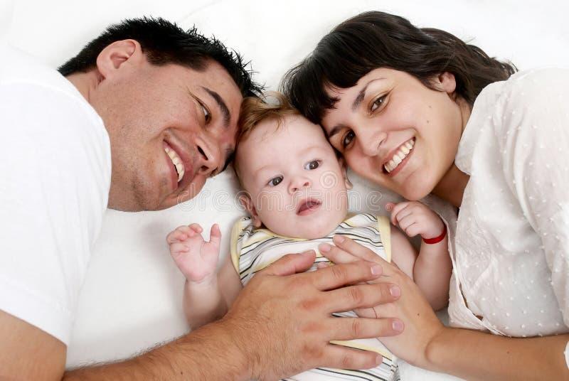 Baby met ouders die op een bed liggen stock fotografie