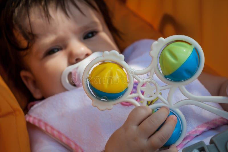 Baby met stuk speelgoed rammelaar stock fotografie