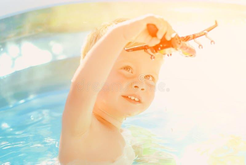 Baby met stuk speelgoed vliegtuig in zwembad Weinig jongen die in openluchtpool leren te zwemmen royalty-vrije stock foto's