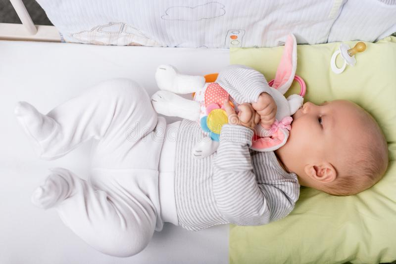 Baby met stuk speelgoed in voederbak stock foto