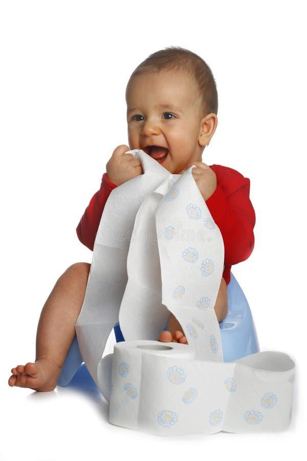 Baby met uitgerold papper stock foto