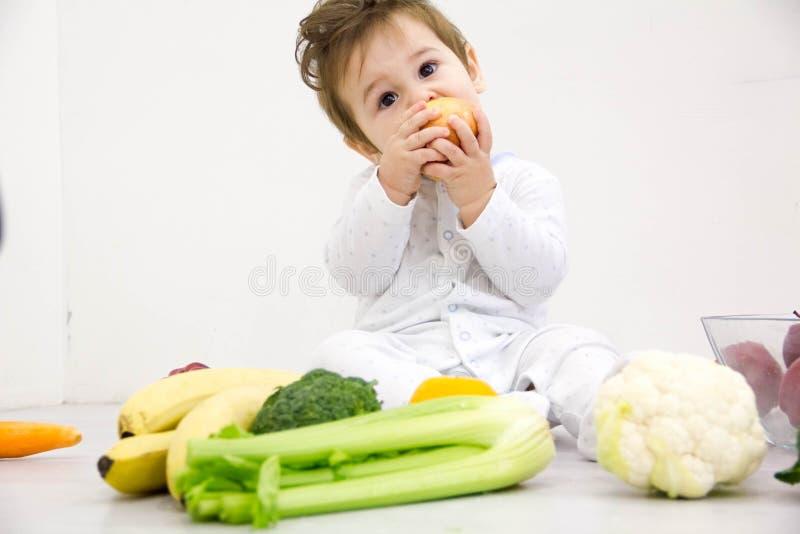 Baby met vruchten en groenten, gezonde kindvoeding wordt omringd die stock foto's
