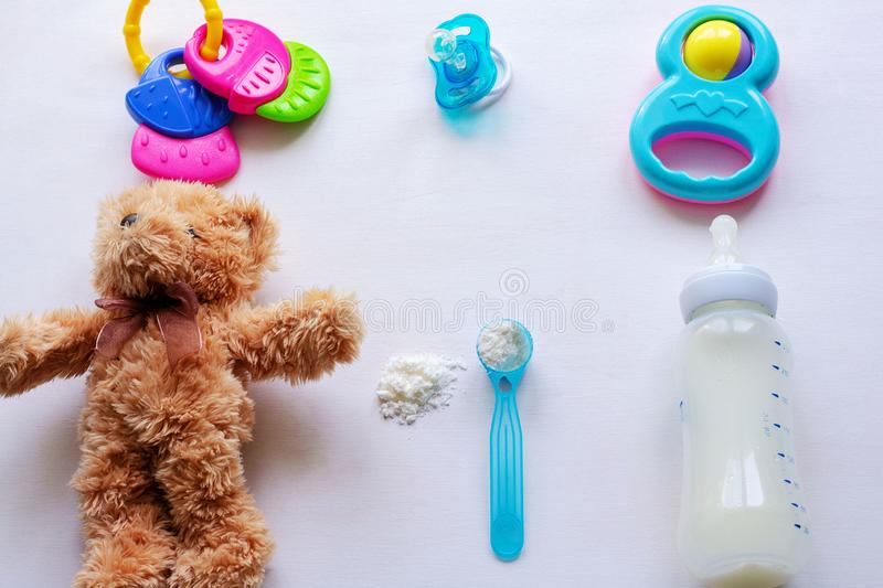 Baby milk powder, baby bottle and children`s toys on a light background flat lay royalty free stock photography