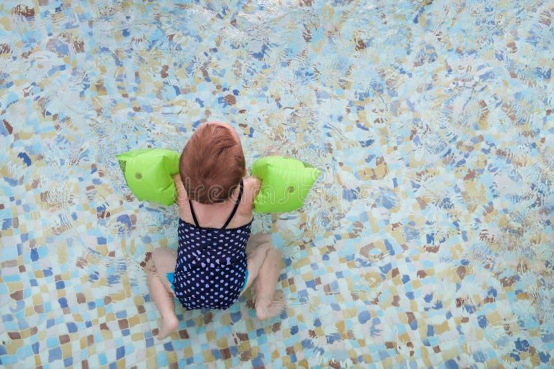 Baby mit aufblasbaren Armbinden Kind, das lernt, im Pool zu schwimmen stockfotos