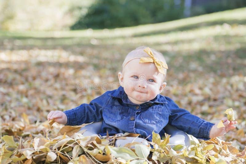 Baby mit Bogen im Kopf, der mit Blättern an einem Fall-Tag spielt stockfoto