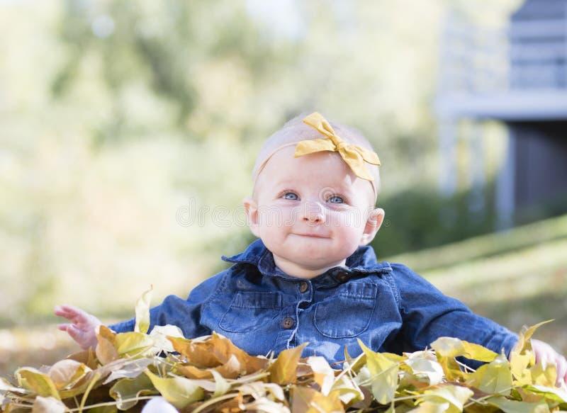 Baby mit Bogen im Kopf, der mit Blättern an einem Fall-Tag spielt stockbild