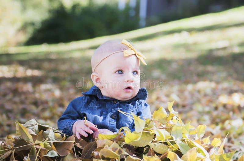 Baby mit Bogen im Kopf, der mit Blättern an einem Fall-Tag spielt stockbilder