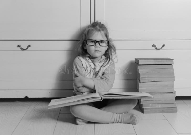 Baby mit dem Buch und Gläsern, die auf dem Boden, Schwarzweiss sitzen stockfoto