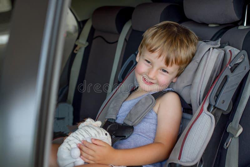 Baby mit dem hellen Haar, das in einem Kinderautositz mit Spielzeug in den Händen sitzt lizenzfreie stockfotografie