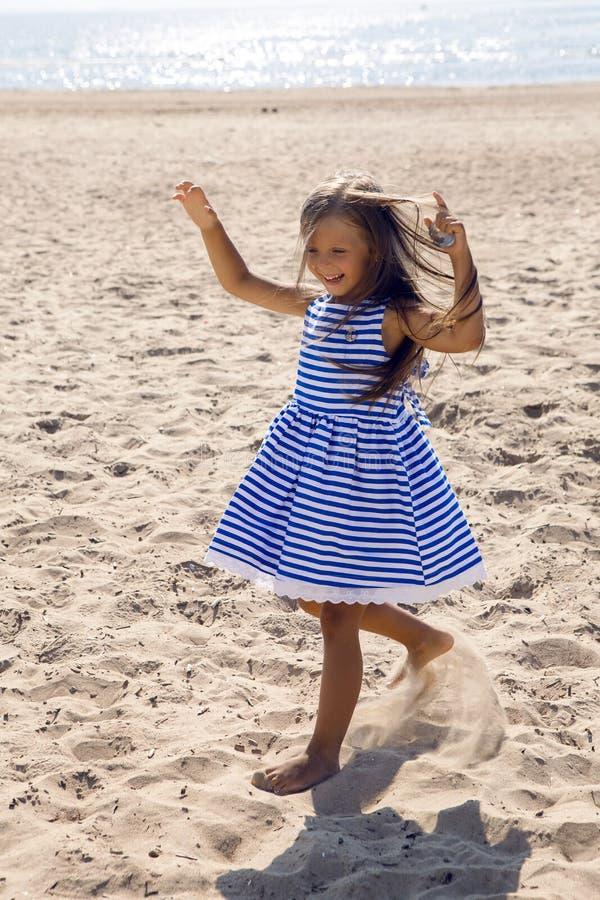 Baby mit dem langen Haar in gestreiftem blauem Kleid lizenzfreie stockfotografie